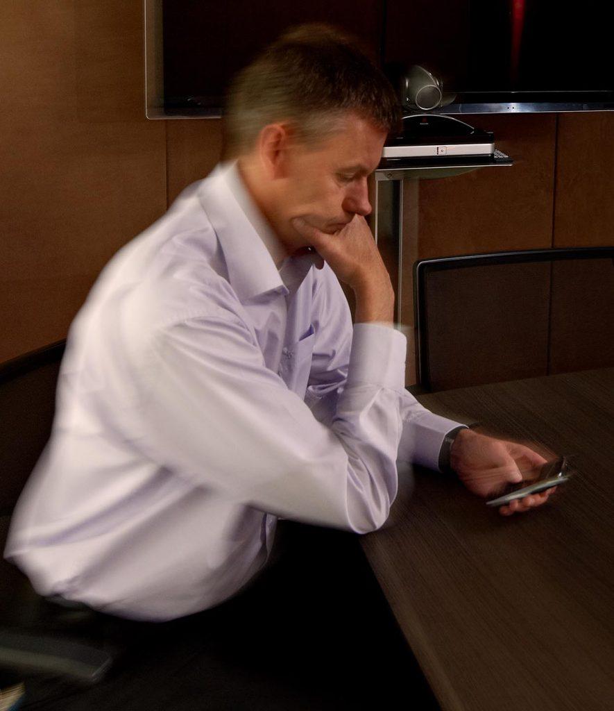 manager kijkt op zijn mobiel