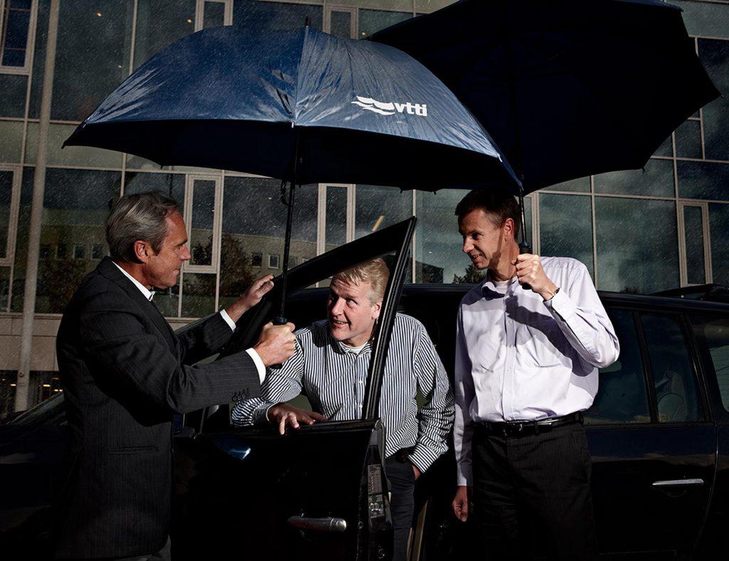 managers in de regen onder paraplu