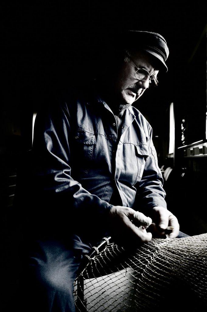 visser die een net aan het boeten is.